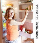 pregnant woman looks for something in fridge at home - stock photo
