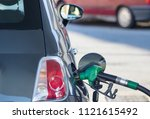 Small photo of fill up with petrol in pumping gas, pumping fuel nozzle gasoline fuel at gas station background.
