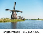 windmills on water canal at... | Shutterstock . vector #1121654522