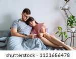 sad couple in bed looking at... | Shutterstock . vector #1121686478