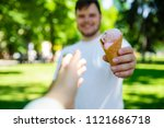 Small photo of man giving ice cream in hot sunny day in city park. first person point of view reach out hand