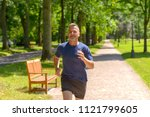 middle aged man jogging along... | Shutterstock . vector #1121799605
