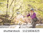 mature adult woman casting fly...   Shutterstock . vector #1121836325