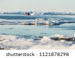 A Kayak moving through Icebergs on the Arctic Ocean