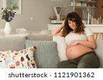 happy pregnant woman sitting... | Shutterstock . vector #1121901362