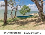 Small photo of Hammock hanging in shade tree shades at lakeside park in Grand Prairie, Texas, USA. Empty hammock with small tent in background. Vacation, relaxation and enjoy the beauty of the nature.