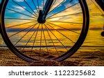 bicycle wheel sunset beach view.... | Shutterstock . vector #1122325682