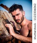 handsome young man standing... | Shutterstock . vector #1122336062