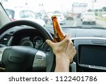 a driver holding alcoholic... | Shutterstock . vector #1122401786