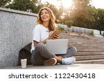 smiling young girl making notes ... | Shutterstock . vector #1122430418