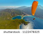 Paragliding in the sky. Paraglider tandem flying over the sea with blue water and mountains in bright sunny day. Aerial view of paraglider and Blue Lagoon in Oludeniz, Turkey. Extreme sport. Landscape - stock photo