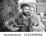 Small photo of Couple in love sit in cafe outdoor, nature background. Girl with happy face fall in love with bearded man, couple reads poems. Romantic couple holds old books with poems. Date and love concept.