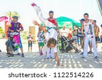 Small photo of SPAIN-TORREVIEJA, ALICANTE, CONCERT ROCK AGAINST CANCER - JUNE 16, 2018: Group of Young People Drum Percussion Clapping. Woman Girl Performs Capoeira Acrobatic Movement Balancing on Hand Upside Down
