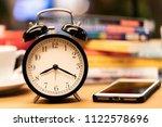 black clock on working  table ... | Shutterstock . vector #1122578696
