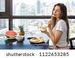young and happy woman is eating ... | Shutterstock . vector #1122653285