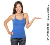 Woman showing your product or message smiling happy isolated on white background in studio. Beautiful multi-racial girl in blue tank top showing open hand palm. - stock photo