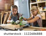 two young girls doing woodwork... | Shutterstock . vector #1122686888