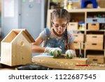 girl building birdhouse in... | Shutterstock . vector #1122687545