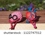 Small photo of Plasticine human heart and brain are sitting on a wooden bench in the park. Disharmonious unhappy person concept