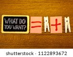 Small photo of Handwriting text What Do You Want Question. Concept meaning Aspiration Contemplation Need Contemplate Aspire White paper clip laid woody desk black slate some texts equal and plus mark.