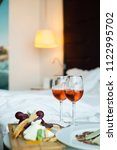 two glass of rose wine  cheese... | Shutterstock . vector #1122995702