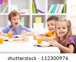 Childhood friends eating together in kids room - stock photo