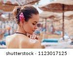 a female  applying sun cream...   Shutterstock . vector #1123017125