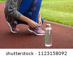 girl tying shoelaces on... | Shutterstock . vector #1123158092