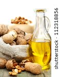 Small photo of Walnut oil and nuts in a bag on a wooden table.