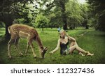 Adorable young lady playing with deer - stock photo