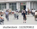Small photo of PYONGYANG, NORTH KOREA - AUGUST 27 2013: Citizens passing by and around a photo processing shop on a hectic warm summer day