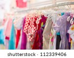 Variety of shirts, trousers, dresses in kids mall - stock photo