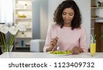 mixed race young woman eating... | Shutterstock . vector #1123409732