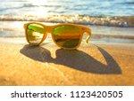 sun glasses on beach near the... | Shutterstock . vector #1123420505