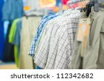 Variety of bright shirts and trousers on stands in supermarket - stock photo