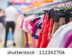 Bright trousers and t-shirts on stands in supermarket - stock photo