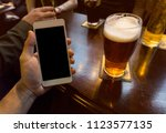 hand holding smartphone in a... | Shutterstock . vector #1123577135