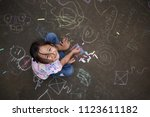 asian small girl with chalk on... | Shutterstock . vector #1123611182