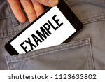 Small photo of Writing note showing Example. Business photo showcasing Illustration Sample Model to follow Guide Explanation For instance Man holding cell phone white screen jean pocket messages application.