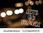 Small photo of Conceptual hand writing showing Let'S Go Travel. Business photo showcasing Going away Travelling Asking someone to go outside Trip Nightlight enlighten reflection thoughts intentions memories.