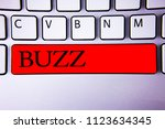 Small photo of Handwriting text writing Buzz. Concept meaning Hum Murmur Drone Fizz Ring Sibilation Whir Alarm Beep Chime Keyboard red key Intention create creating message idea communicate paper.