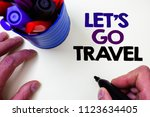 Small photo of Writing note showing Let'S Go Travel. Business photo showcasing Going away Travelling Asking someone to go outside Trip Blue pen holder white background shadow lovely message idea temple.