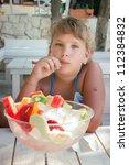 Girl eating fruit salad - stock photo