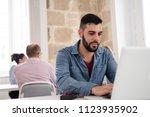 bearded man in a blue shirt... | Shutterstock . vector #1123935902
