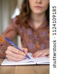woman is writing on a desk ... | Shutterstock . vector #1124109185