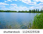 large dark lake in the forest... | Shutterstock . vector #1124225528