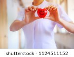 red smiling heart held by... | Shutterstock . vector #1124511152