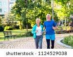 happy senior couple jogging... | Shutterstock . vector #1124529038
