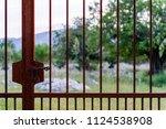 closed rusty gate to a garden... | Shutterstock . vector #1124538908