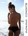 beautiful woman standing on the beach topless.back view.close up.
